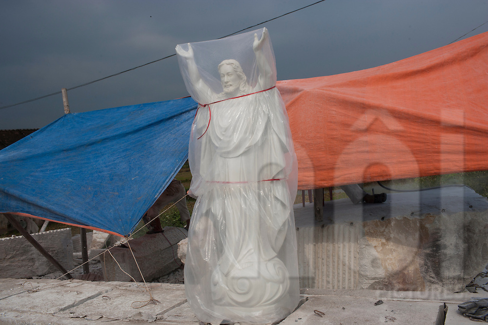 A plastic wrapped Catholic statue sits on the pavement outside of a factory in Nam Dinh, Vietnam, Southeast Asia