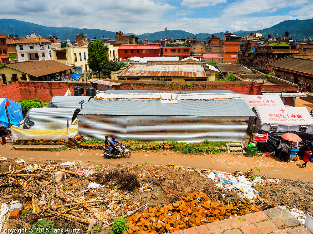 02 AUGUST 2015 - BHAKTAPUR, NEPAL:  A small Internal Displaced Person (IDP) camp at Durbar Square in Bhaktapur for people left homeless by the Nepal earthquake. The Nepal Earthquake on April 25, 2015, (also known as the Gorkha earthquake) killed more than 9,000 people and injured more than 23,000. It had a magnitude of 7.8. The epicenter was east of the district of Lamjung, and its hypocenter was at a depth of approximately 15km (9.3mi). It was the worst natural disaster to strike Nepal since the 1934 Nepal–Bihar earthquake. The earthquake triggered an avalanche on Mount Everest, killing at least 19. The earthquake also set off an avalanche in the Langtang valley, where 250 people were reported missing. Hundreds of thousands of people were made homeless with entire villages flattened across many districts of the country. Centuries-old buildings were destroyed at UNESCO World Heritage sites in the Kathmandu Valley, including some at the Kathmandu Durbar Square, the Patan Durbar Squar, the Bhaktapur Durbar Square, the Changu Narayan Temple and the Swayambhunath Stupa. Geophysicists and other experts had warned for decades that Nepal was vulnerable to a deadly earthquake, particularly because of its geology, urbanization, and architecture.      PHOTO BY JACK KURTZ