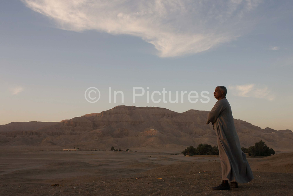 A local Egyptian businessman looks thoughtfully into a setting sun while on sand dunes of a desert enviroment, near a village on the West Bank of Luxor, Nile Valley, Egypt. Hamdy Mosa has worked in the tourism industry all of his adult life and now heads a family business dependent on the industry, currently enduring a downturn in visitor numbers after recent terrorist activity. (Photo by Richard Baker / In Pictures via Getty Image).
