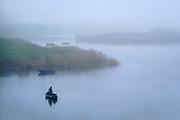 Nederland, 31-12-2019Een visser, sportvisser, in zijn roeiboot vist met een hengel in de oude waal terwijl het mistig weer is . Foto: Flip Franssen
