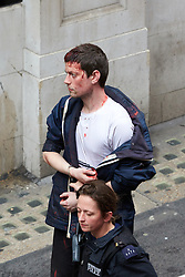 © Licensed to London News Pictures.  11/06/2013. LONDON, UK. An arrested anti G8 protester, with a head injury, is escorted  by a police officer.  Photo credit: Cliff Hide/LNP