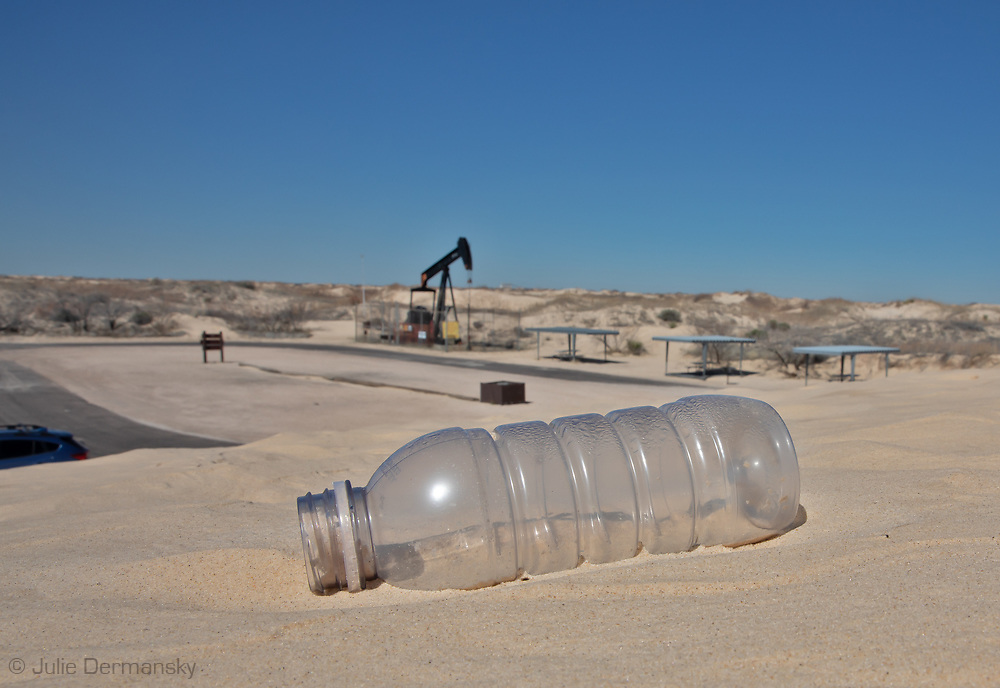 A pump jack and and empty plastic bottle at the Great Sand Dunes National Park & Preserve in the Permain Basin.