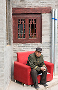An elderly man sits on a red chair in a hutong, or alley way in the popular Haohai neighborhood in central Beijing.