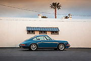 Auto Cinema from Automotive Car Photographer Randy Wells, Image of a blue coupe in front of quonset hut, 1973 Porsche 911 E in southern California, property released