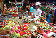 INDONESIA, BALI, CEREMONIES offerings of food and flowers being blessed by the priest at the village temple