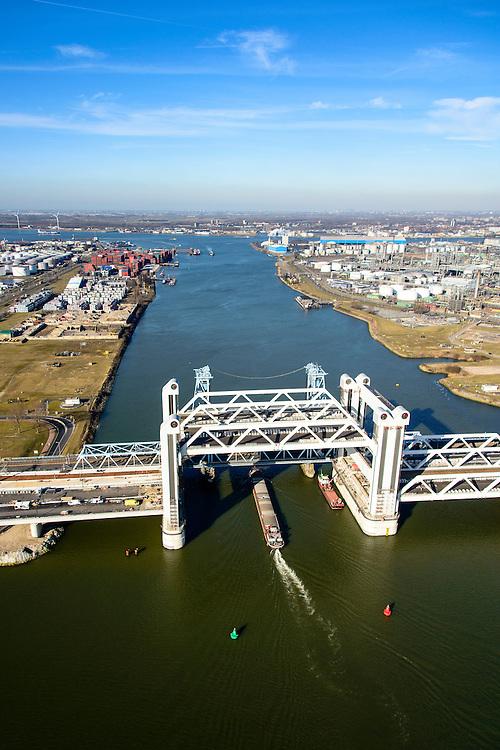 Nederland, Zuid-Holland, Rotterdam, 18-02-2015; bouw van de nieuwe Botlekbrug, binnenvaartschip passeert de nieuwe brug. De brug over de Oude Maas is een hefbrug, een van de twee brugdelen in geheven toestand. De heftorens van de oude brug gaan verscholen achter de nieuwe brug.<br /> Construction of the new Botlek bridge.<br /> The bridge over the Oude Maas is a vertical-lift bridge or lift bridge, one of the two bridge sections raised. <br /> luchtfoto (toeslag op standard tarieven);<br /> aerial photo (additional fee required);<br /> copyright foto/photo Siebe Swart