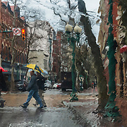 A small group crosses Quarrier Street on a rainy day in downtown Charleston W.V., on Tuesday, February 12, 2019. Photo taken through a rain soaked windshield.