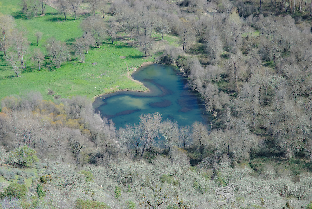 Aerial picture of trees and lake in the Rogue Valley from Lower Table Rock which is one of two prominent volcanic plateaus located just north of the Rogue River in Jackson County, Oregon. Shaped by erosion, they now stand about 800 feet (240 m) above the surrounding Rogue Valley.