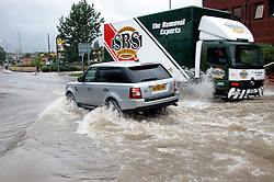 Torrential rain causes flooding and traffic chaos as vehicles try to make thier way through floodwater on The Common Ecclesfield Sheffield South Yorkshire.25 June 2007.Image COPYRIGHT Paul David Drabble.