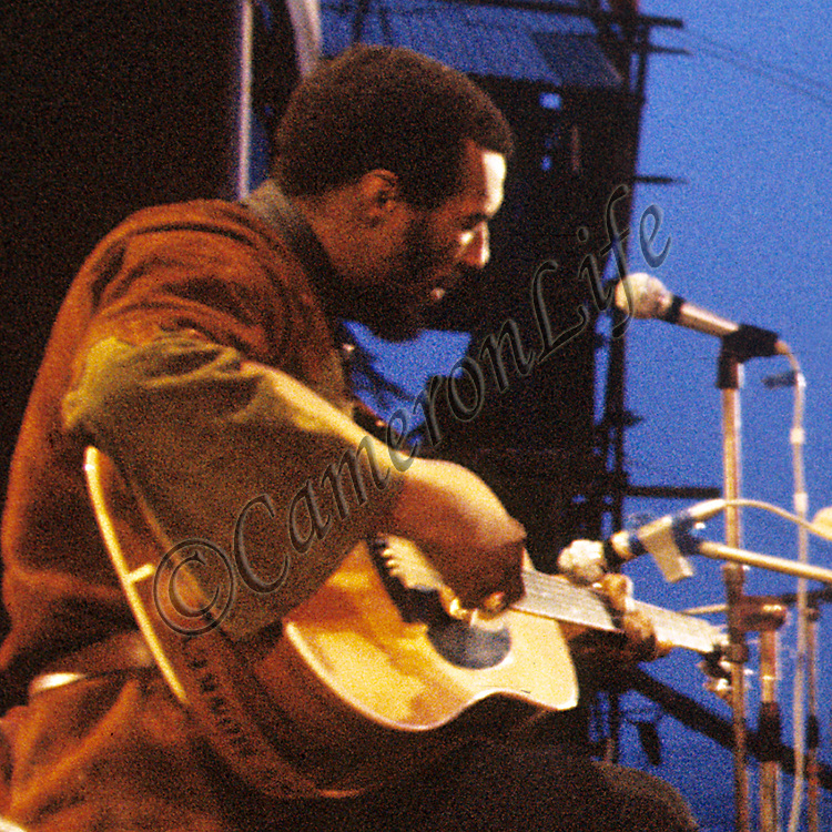 """Richie Havens .- .Richie Havens was the man chosen to close the 1970 Pop Festival along with his regular guitarist Paul Williams. As the sun rose Havens played """"Here Comes the Sun"""". Author Brian Hinton having interviewed Charles for his book says """"Charles Everest, whenever about to photograph him, recalls that Havens turned his head to show off his impressive profile""""!"""