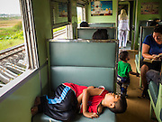 19 MARCH 2015 - AYUTTHAYA, AYUTTHAYA, THAILAND:   A child sleeps on a seat on the third class train from Ayutthaya to Bangkok. The train line from Bangkok to Ayutthaya was the first rail built in Thailand and was opened in 1892. The State Railways of Thailand (SRT), established in 1890, operates 4,043 kilometers of meter gauge track that reaches most parts of Thailand. Much of the track and many of the trains are poorly maintained and trains frequently run late. Accidents and mishaps are also commonplace. Successive governments, including the current military government, have promised to upgrade rail services. The military government has signed contracts with China to upgrade rail lines and bring high speed rail to Thailand. Japan has also expressed an interest in working on the Thai train system. Third class train travel is very inexpensive. Many lines are free for Thai citizens and even lines that aren't free are only a few Baht. Many third class tickets are under the equivalent of a dollar. Third class cars are not air-conditioned.   PHOTO BY JACK KURTZ