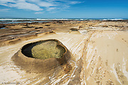 "This large reef formed the base of huge sand-dune headlands at East Cinsta in the Eastern Cape of South Africa. I'm no geologist sadly, but the reef appeared to be a mix of sandstone and other sedimentary rocks. I cannot work out how these amazing and quite surreal rock baths were formed. At low tide these 2-5ft raised 'baths' were revealed. I'm guessing the sides are a harder rock than the surrounding material, but I can't work out how the erosion took place to leave the pools. on other stretches of the reef, dark nodules of rock (from 2-7"") appeared as if loose stones scattered on the surface, but in fact were solidly attached to the reef itself.<br /> .<br /> I do wish I'd studied geology a lot further than A-level geography!"