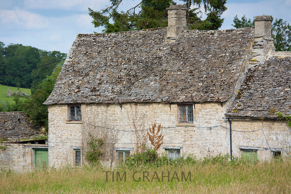 Traditional cottage with Cotswold stone roof tiles at Sherborne in The Cotswolds, Gloucestershire, UK