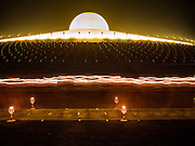 """11 FEBRUARY 2016 - KHLONG LUANG, PATHUM THANI, THAILAND: Buddhist monks participate in a candlelight procession around the pagoda during the Makha Bucha Day service at Wat Phra Dhammakaya.  Makha Bucha Day is a public holiday in Cambodia, Laos, Myanmar and Thailand. Many people go to the temple to perform merit-making activities on Makha Bucha Day, which marks four important events in Buddhism: 1,250 disciples came to see the Buddha without being summoned, all of them were Arhantas, or Enlightened Ones, and all were ordained by the Buddha himself. The Buddha gave those Arhantas the principles of Buddhism. In Thailand, this teaching has been dubbed the """"Heart of Buddhism."""" Wat Phra Dhammakaya is the center of the Dhammakaya Movement, a Buddhist sect founded in the 1970s and led by Phra Dhammachayo. Makha Bucha Day is one of the most important holy days on the Thai Buddhist calender.      PHOTO BY JACK KURTZ"""
