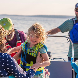 A family arrives by boat on East Gosling Island in Casco Bay, Harpswell, Maine.