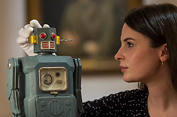 "© Licensed to London News Pictures. 19/03/2021. LONDON, UK. A staff member views a ""rare TM (Masudaya) battery-operated Radicon Robot, 1957"" (est. £4,000-6,000).  Preview of the upcoming sale of property from the collection of the Patricia Knatchbull, 2nd Countess Mountbatten of Burma.  Over 350 lots spanning jewellery, furniture, paintings, sculpture, books, silver, ceramics & objets d'art are to be auctioned on 24 March at Sotheby's New Bond Street galleries.  Photo credit: Stephen Chung/LNP"