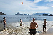 Men playing football on Niteroi beach with a view of the Guanabara bay, Christ the Reedemer statue and the Sugar Loaf mountain, Rio de Janeiro.