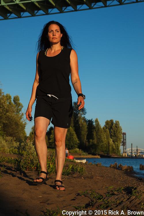 USA, Oregon, Portland, Cathedral Park, woman walking along the beach at Cathedral Park near the St. John's Bridge. MR