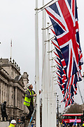 "A man is mounting British Union flags outside Parliament near the statue of Winston Churchill in London, Thursday, Jan. 30, 2020. Although Britain formally leaves the European Union on Jan. 31, little will change until the end of the year. Britain will still adhere to the four freedoms of the tariff-free single market "" free movement of goods, services, capital and people. (Photo/Vudi Xhymshiti)"
