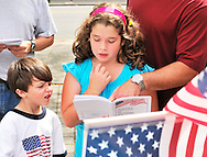 Girl reading Declaration of Independence at July 4th Celebration, with father pointing to part in book, and young boy looking on. Merrick, New York, July 4, 2011.