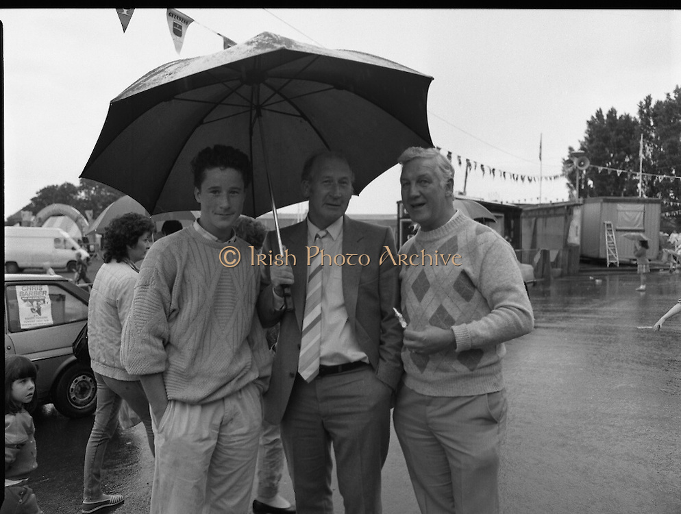 """Guinness Family Day At The Iveagh Gardens. (R83)..1988..02.07.1988..07.02.1988..2nd  July 1988..The family fun day for Guinness employees and their families took place at the Iveagh Gardens today. Top at the bill at the event were """"The Dubliners"""" who treated the crowd to a performance of all their hits. Ireland's penalty hero from Euro 88, Packie Bonner, was on hand to sign autographs for the fans...A sudden downpour didn't dampen the spirits as these men pose for a picture."""