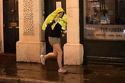 © Licensed to London News Pictures. 20/10/2021. London, UK. A woman shelters under a coat she runs during heavy rain in Greenwich South East London. An Amber weather warning for rain is in place for parts of London and South East England.  Photo credit: George Cracknell Wright/LNP