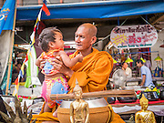 02 NOVEMBER 2012 - HAT YAI, SONGKHLA, THAILAND: A Buddhist monks holds a baby while blessing it in Hat Yai, Songkhla, Thailand. Hat Yai is the commercial center of south Thailand and a popular weekend vacation destination for Malaysian and Singaporean tourists.    PHOTO BY JACK KURTZ