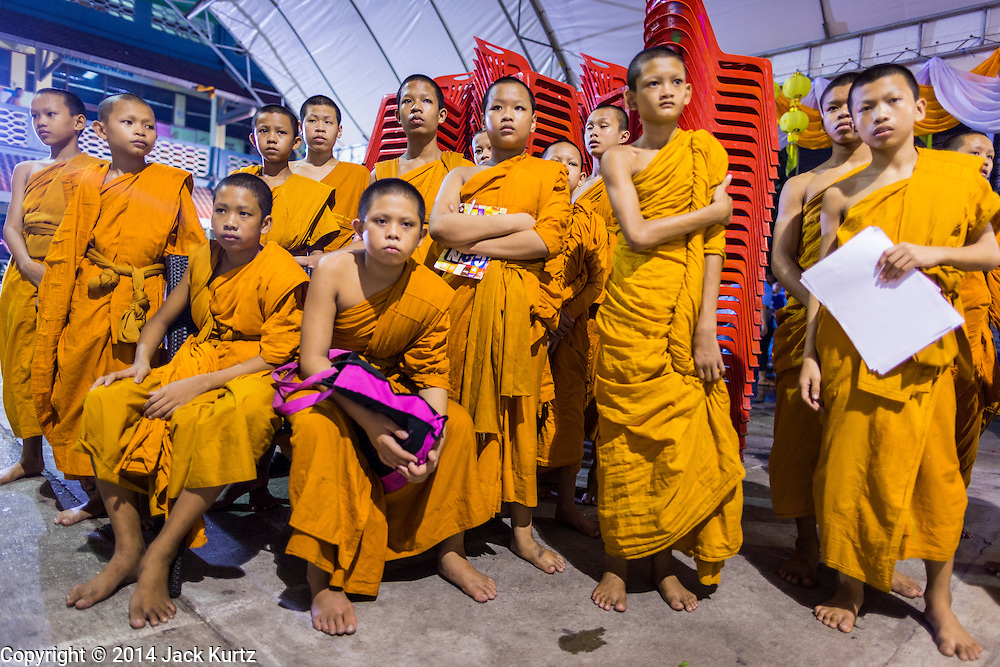 01 OCTOBER 2014 - BANGKOK, THAILAND: Buddhist novices watch a religious service at Wat Yannawa (also spelled Yan Nawa) during the Vegetarian Festival in Bangkok. The Vegetarian Festival is celebrated throughout Thailand. It is the Thai version of the The Nine Emperor Gods Festival, a nine-day Taoist celebration beginning on the eve of 9th lunar month of the Chinese calendar. During a period of nine days, those who are participating in the festival dress all in white and abstain from eating meat, poultry, seafood, and dairy products. Vendors and proprietors of restaurants indicate that vegetarian food is for sale by putting a yellow flag out with Thai characters for meatless written on it in red.     PHOTO BY JACK KURTZ