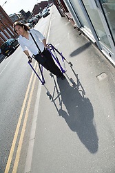 Young woman with walking frame walking down the street,