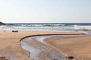 Two people lying by sea on sandy Praia Carvalhal beach, Brejão, Alentejo Littoral, Portugal, Southern Europe