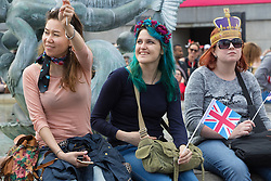 Trafalgar Square, London, June 12th 2016. Rain greets Londoners and visitors to the capital's Trafalgar Square as the Mayor hosts a Patron's Lunch in celebration of The Queen's 90th birthday. PICTURED: Young women enjoy the events in Trafalgar Square.