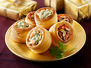 Volavents filled with salmon & dill cream and olive tapenade on a gold plate with gold presents