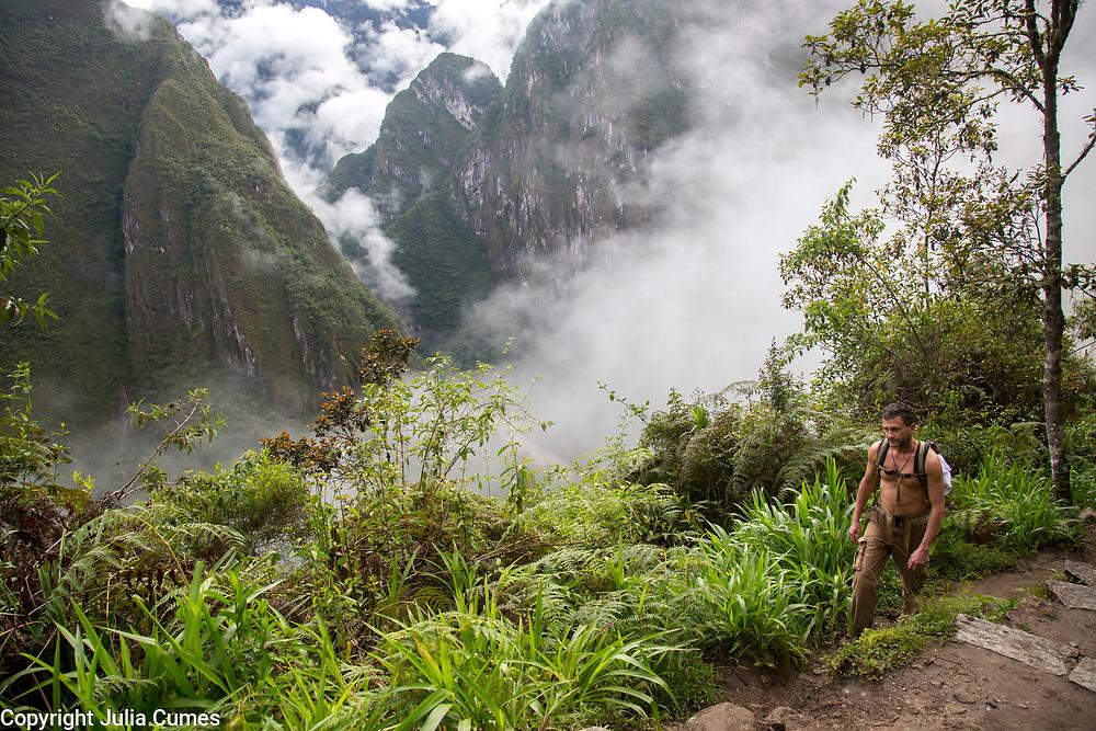 A man hikes the steep path to the ancient site of Machu Pichu in Cusco, Peru.