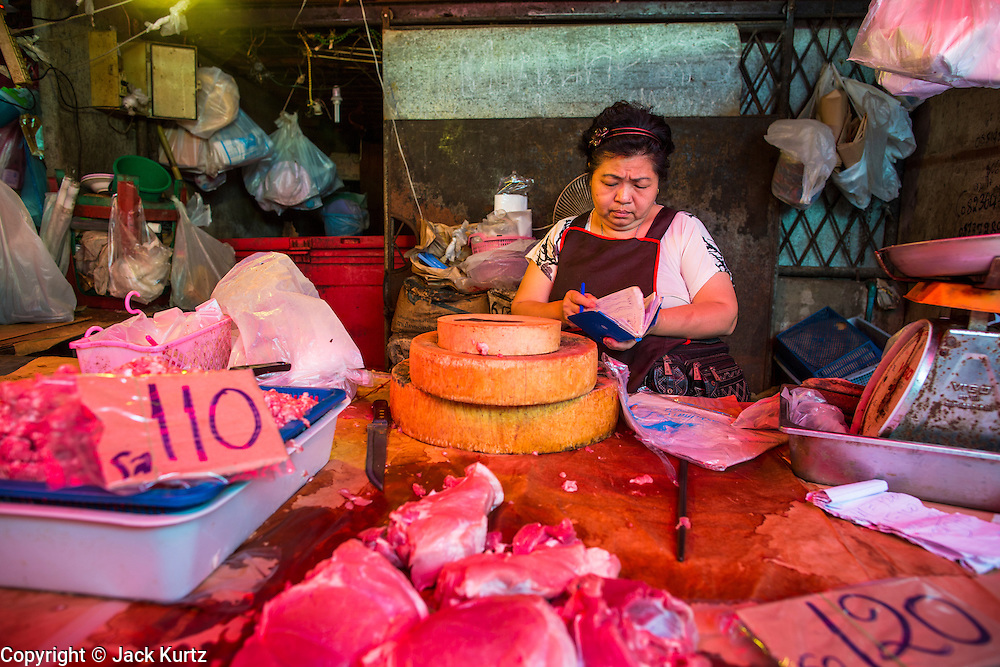 17 JANUARY 2013 - SAMUT SONGKHRAM, SAMUT SONGKHRAM, THAILAND: A meat vendor counts her money in the Samut Songkhram market. Four trains each day make the round trip from Baan Laem, near Samut Sakhon, to Samut Songkhram, the train chugs through market eight times a day (coming and going). Each time market vendors pick up their merchandise and clear the track for the train, only to set up again when the train passes. The market on the train tracks has become a tourist attraction in this part of Thailand and many tourists stop to see the train on their way to or from the floating market in Damnoen Saduak.    PHOTO BY JACK KURTZ