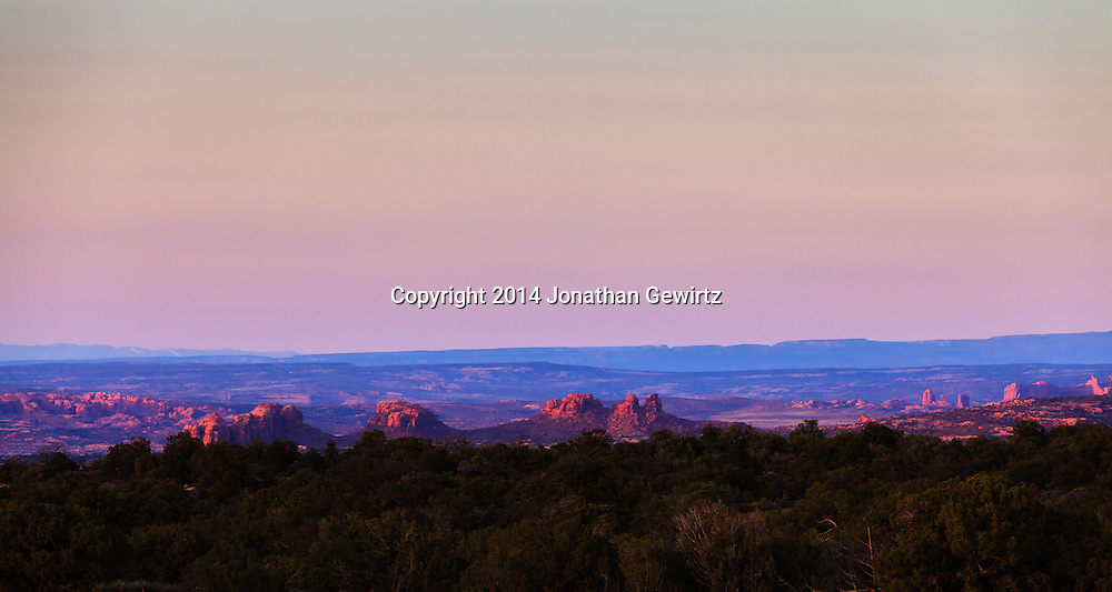 The desert floor glows red in the last rays of the setting sun in this view from the high plateau northwest of Moab, Utah.<br /> WATERMARKS WILL NOT APPEAR ON PRINTS OR LICENSED IMAGES.