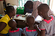 The Wema centre facilitates health clinics organised by the local government hospital. There are weekly health care sessions including a VCT clinic.  Arnold Maitha Baya the VCT counsellor tests a woman and her 3 daughters for HIV. The twins aged 5 and eldest daughter age 7 were all given a clear result. The mother found out she was positive.
