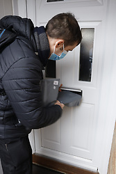 © Licensed to London News Pictures. 02/02/2021. Woking, UK. Covid testing kits are distributed to residents in Goldsworth Park, Woking in Surrey, where cases of the South African variant of Covid-19 have been found. Public health England are carring out surge testing for selected parts of the Goldsworth Park, St Johns and Knaphill areas of Woking this week. Photo credit: Peter Macdiarmid/LNP