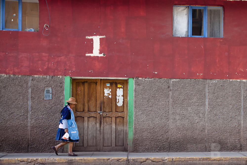 A peruvian women walks along downtown Pisac, Peru with traditional clothing and hat.