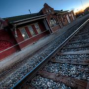 Old train depot in Stafford KS with vanishing point down railroad tracks at sunset.