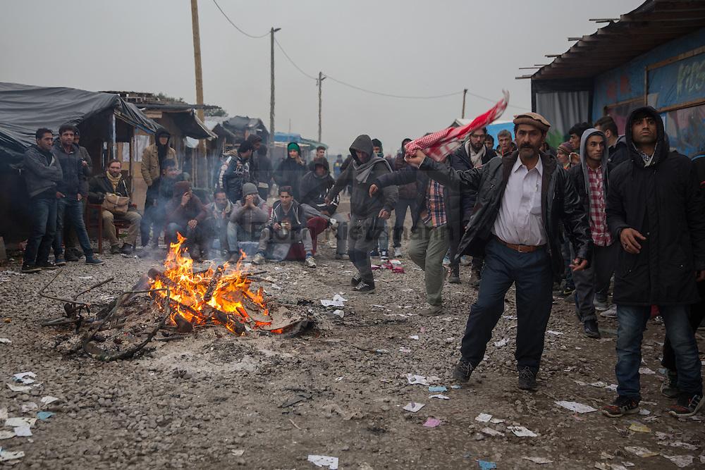 """Calais, Pas-de-Calais, France - 24.10.2016    <br />  <br /> Refugees dance arround a fire. Start of the eviction on the so called """"Jungle"""" refugee camp on the outskirts of the French city of Calais. Refugees and migrants leaving the camp to get with buses to asylum facilities in the entire country. Many thousands of migrants and refugees are waiting in some cases for years in the port city in the hope of being able to cross the English Channel to Britain. French authorities announced a week ago that they will evict the camp where currently up to up to 10,000 people live.<br /> <br /> Fluechtlinge tanzen um ein Feuer herum. Beginn der Raeumung des so genannte """"Jungle""""-Fluechtlingscamp in der französischen Hafenstadt Calais. Fluechtlinge und Migranten verlassen das Camp um mit Bussen zu unterschiedlichen Asyleinrichtungen gebracht zu werden. Viele tausend Migranten und Fluechtlinge harren teilweise seit Jahren in der Hafenstadt aus in der Hoffnung den Aermelkanal nach Großbritannien ueberqueren zu koennen. Die franzoesischen Behoerden kuendigten vor einigen Wochen an, dass sie das Camp, indem derzeit bis zu bis zu 10.000 Menschen leben raeumen werden. <br /> <br /> Photo: Bjoern Kietzmann"""