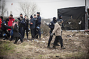 March 1, 2016 - Calais, France -<br /> <br /> Destruction Of Calais Jungle Camp Continues<br /> <br /> Policemen stand next to migrants as agents dismantle shacks on March 1, 2016 in the ''Jungle'' migrant camp in the French northern port city of Calais. Authorities return to clear migrant shelters from more parts of the 'Jungle' migrant camp in Calais and try to move people to shipping containers on another part of the site. French demolition teams began dismantling huts yesterday. Resistance is expected to continue and overnight riot police fired teargas at migrants who were throwing stones. A court ruling on Thursday approved a French Govt plan to clear part of the site. Authorities say approx 1,000 migrants are to be affected out of 3,700 people - many of them refugees from Syria and Iraq - who are thought to live in the camp. Mayor of Calais Natacha Bouchart has demanded the closure of the site for several weeks following several recent clashes with police <br /> ©Exclusivepix Media