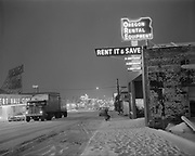 Y-551117-01.  Night view of Oregon Rental & Equipment Service Co. 955 NE Union. Union Ave. looking south in snow. Area south of Holladay St.  The Oregon Convention Center is built on this site. November 17, 1955.