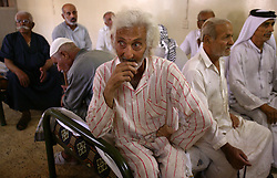 Najim Al Deen Najef, 70, waits to be seen by a South Korean humanitarian organization at a retirement home in Sadr City, Baghdad, Iraq, July 22, 2003. Even though most families in Iraq care for their aging relatives at home, there is still a need for the facility, which is the largest of its kind in Baghdad housing 45 women and 87 men. The facility was not looted during the war, but it is still lacks some funding and is in need of medications for patients with chronic conditions such as heart disease and diabetes.