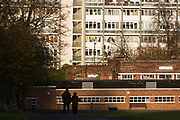 A couple walking downhill are silhouetted against autumn sunshine, against high-rise flats and Brixton Lido seen from Brockwell Park, Herne Hill SE24. Making their way towards the brown brick of the Lido and the brighter, more modern materials of the flats, we see a scene of partnership and togetherness, where people otherwise live isolated and anonymously in an inner-city like London. Brockwell Park is a 50.8 hectare (125.53 acres) park located between Brixton, Herne Hill and Tulse Hill. Brockwell Hall house and its grounds were acquired by the London County Council (LCC) in March 1891 and opened to the public the following summer. In 1901 the LCC acquired a further 43 acres (17 ha) of land north of the original park.