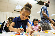 A young family get to spend some extended time together during a family visit in HMP Brixton, South London on the 26th of July 2016, London United Kingdom. The Prisoner Advice & Care Trust (PACT) organise special family days that help the men inside the prison connect with and support their partners and children on the outside. (photo by Andy Aitchison)