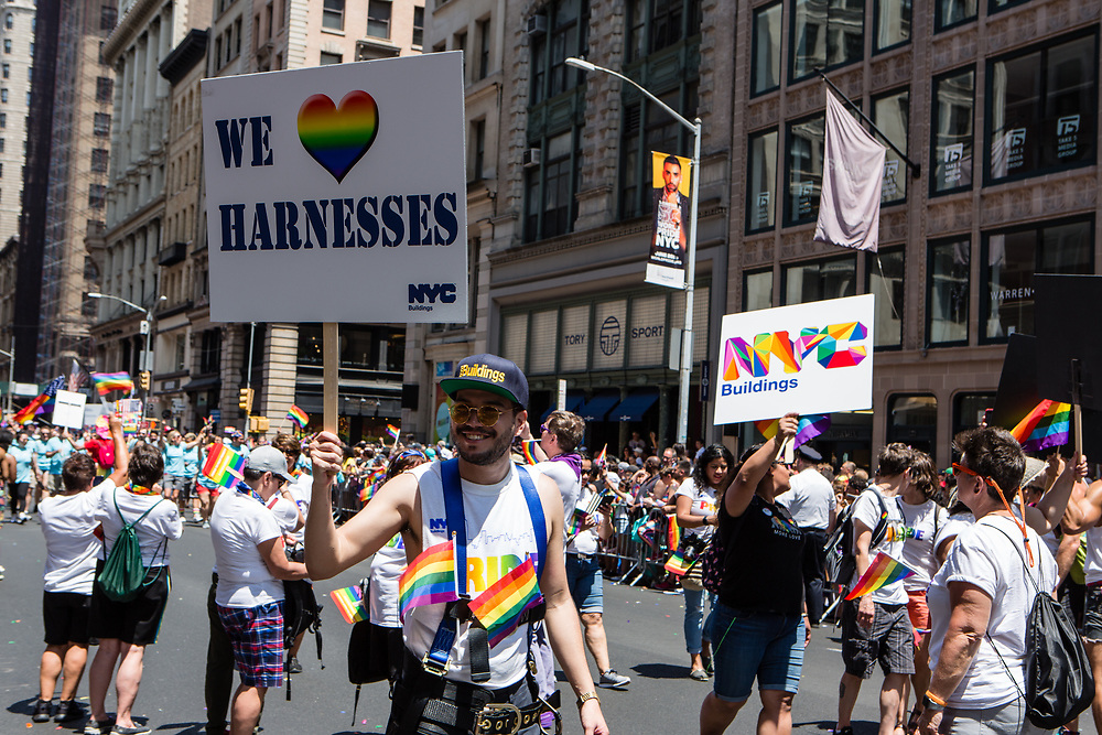 """New York, NY - 30 June 2019. The New York City Heritage of Pride March filled Fifth Avenue for hours with participants from the LGBTQ community and it's supporters. A grop from NYC Buildings, one of whom carries a sign reading """"We [rainbow colored heart] Harnesses."""""""
