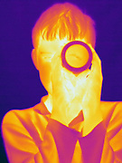 Thermogram of a boy looking through a germanium oxide lens. This image has a corresponding visible light image.  This lens is opaque to visible light, but is transparent to far-infrared light.  This image was taken inthe far-infrared.  The different colors represent different temperatures on the object. The lightest colors are the hottest temperatures, while the darker colors represent a cooler temperature.  Thermography uses special cameras that can detect light in the far-infrared range of the electromagnetic spectrum (900?14,000 nanometers or 0.9?14 µm) and creates an  image of the objects temperature..