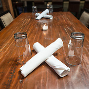A simple table setting in a restaurant, with a wooden table and the silverware wrapped in plane white napkins.