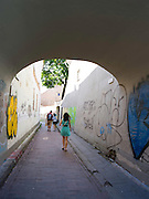 Students walk along a graffiti-covered alley in Senamiestyje/Old Town, Vilnius, Lithuania