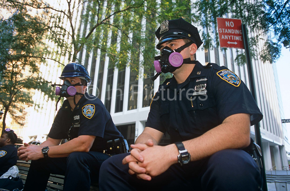 The Monday morning following the attacks on September 11th we see two officers of the NYPD wearing dust masks to protect themselves from the ambient pollution that pervaded the air in Manhattan weeks after the terrorist devastation at Ground Zero. The two policemen rest on the back of a bench near Wall Street whose financial institutions were so disrupted. Days after the historical events and to help maintain a comforting police presence, the police and National Guard were on every street corner, security being prominent at all nationally symbolic institutions and buildings. As a show of force, it was also a clear deterrent for would-be petty criminals when New Yorkers felt vulnerable to further attack.